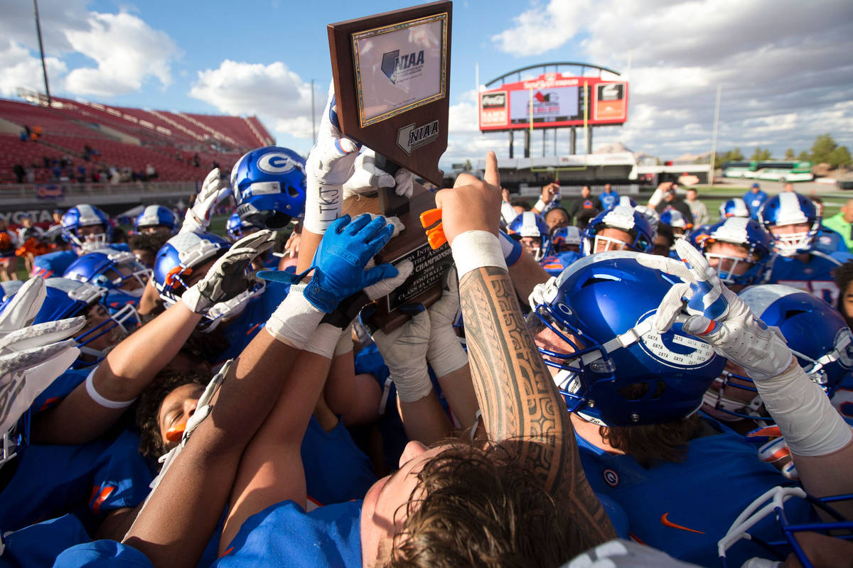 Bishop Gorman players celebrate with the trophy after defeating Reno's Bishop Manogue 69-26 in ...
