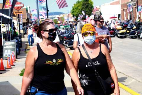 Women walk during opening day of the 80th annual Sturgis Motorcycle Rally in Sturgis, S.D., in ...