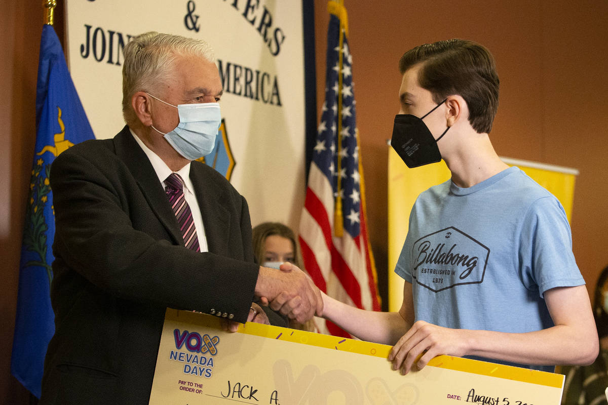 Jack A. shakes Gov. Steve Sisolak's hand after winning a $20,000 college savings plan during th ...