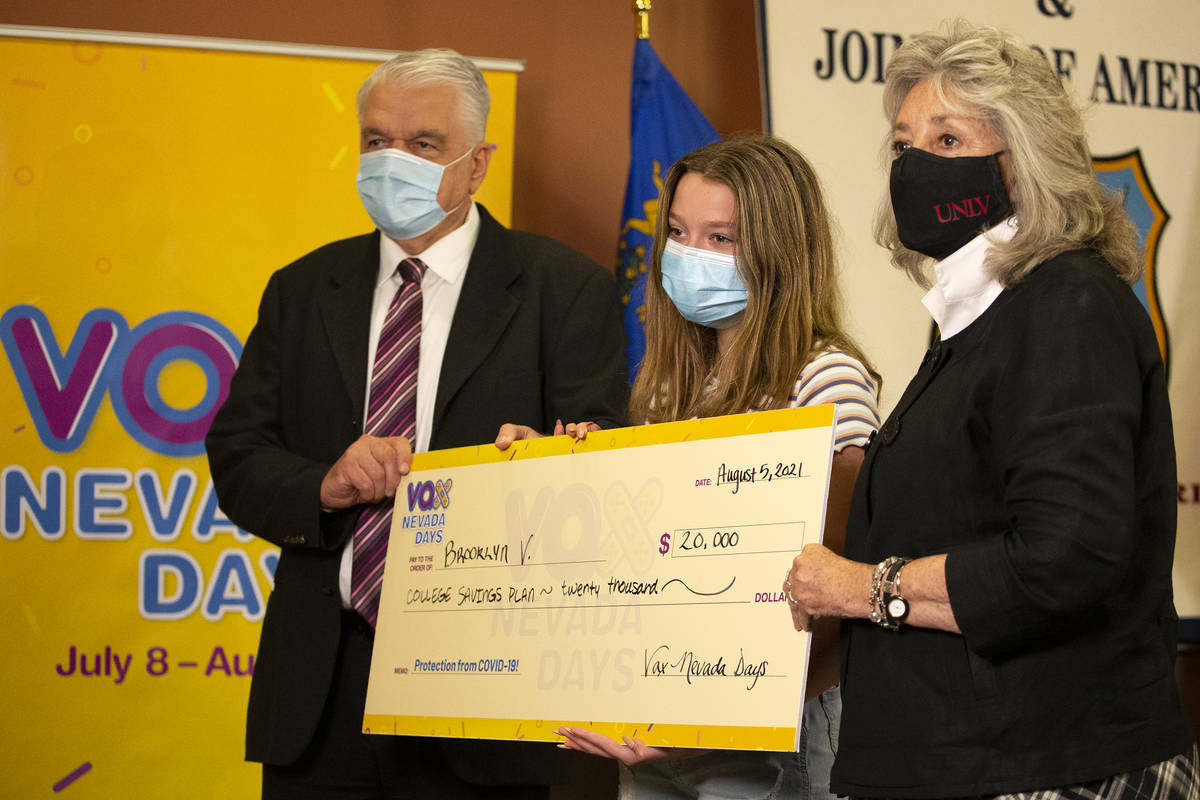 Brooklyn V., who won a $20,000 college savings plan, poses for photos with Gov. Steve Sisolak a ...