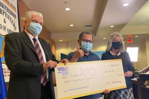 Edward M. of North Las Vegas holds his novelty check of $25,000 with Gov. Steve Sisolak, left, ...