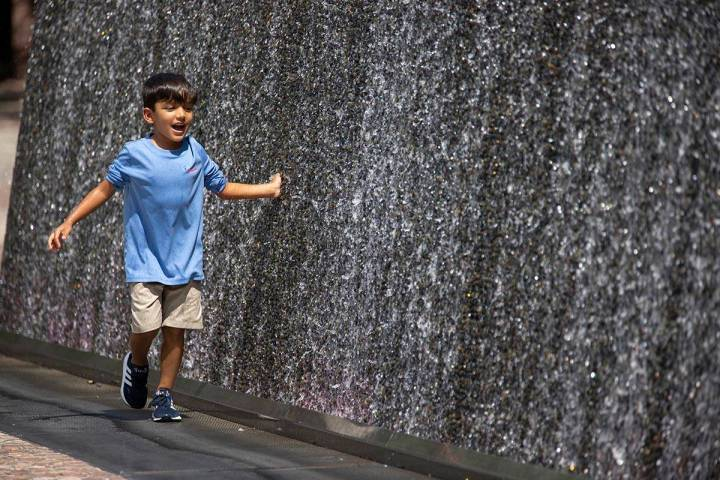 Ian Alaniz, 5, of Dublin, Texas, touches a water feature outside of the New York-New York hotel ...