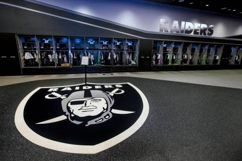 A large logo is painted on the floor in the expansive locker room within the Las Vegas Raiders ...