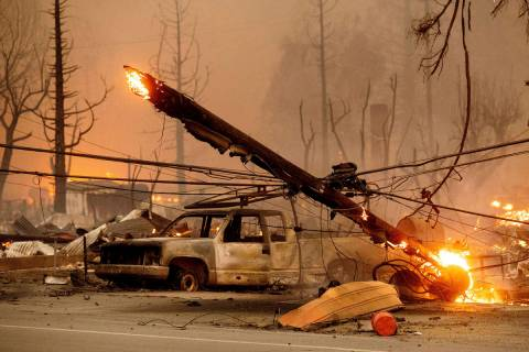 A utility pole burns as the Dixie Fire tears through the Greenville community of Plumas County, ...