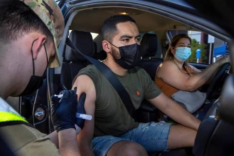 Nevada National Guard SPC Austin Czarnecki gives a COVID-19 vaccination to Luis Gerardo with Hi ...