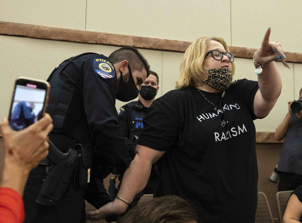 A protester, protesting against a COVID-19 mandate, reacts as she was arrested and escorted out ...