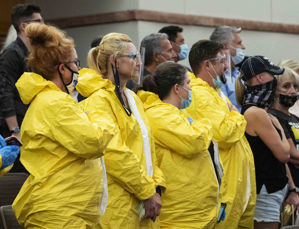 Protesters, including Norma Scurlock, left, wear hazmat suits as they protest against a COVID-1 ...
