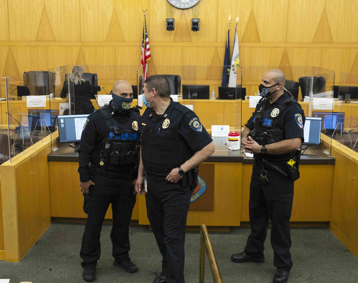 The Clark County School District police officers stand guard after protesters against a COVID-1 ...
