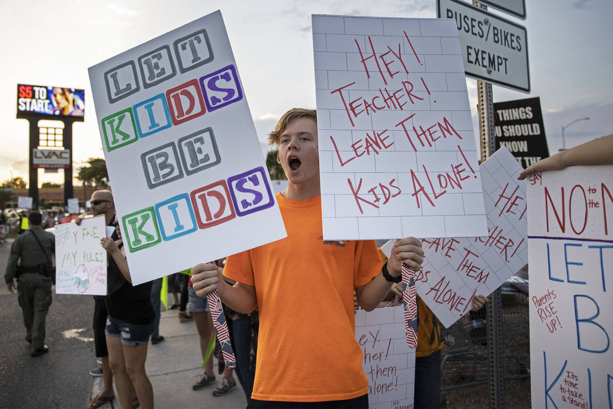 Jacob Dennon holds a sign opposing the mask mandate for Clark County School District students o ...