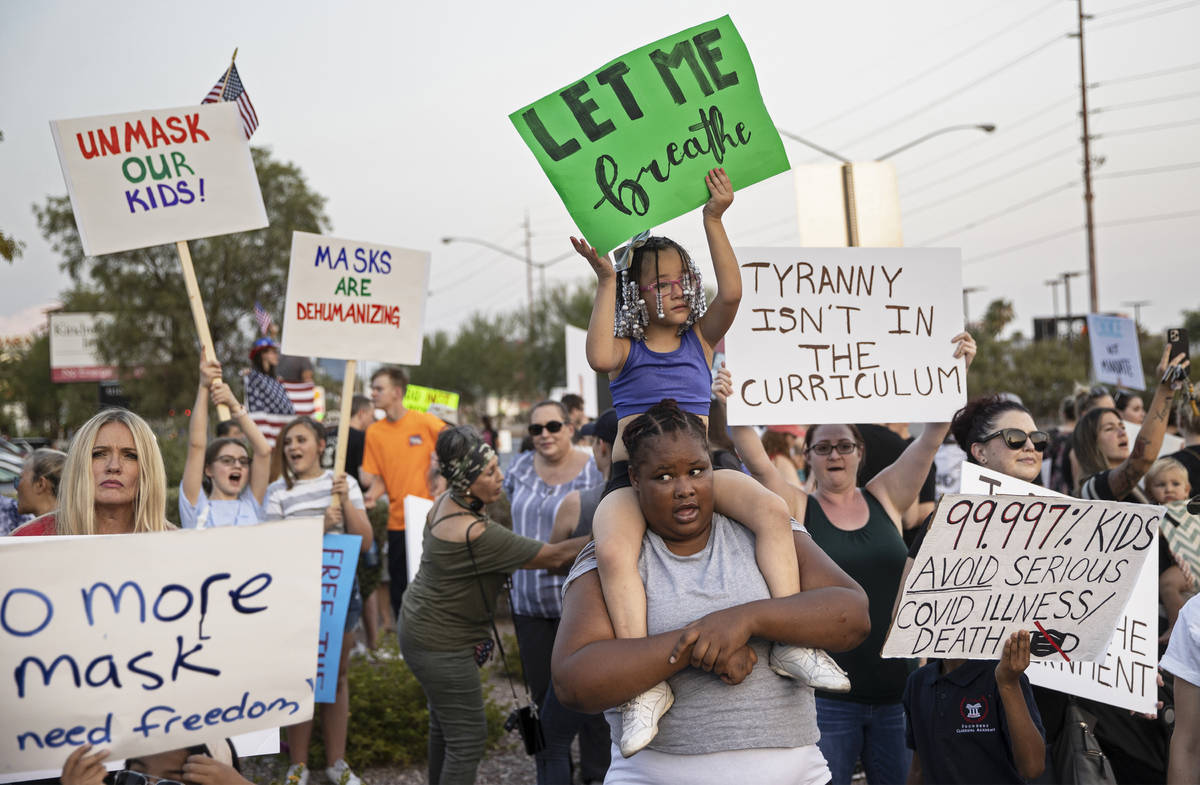 Protesters hold signs opposing the mask mandate for Clark County School District students on We ...