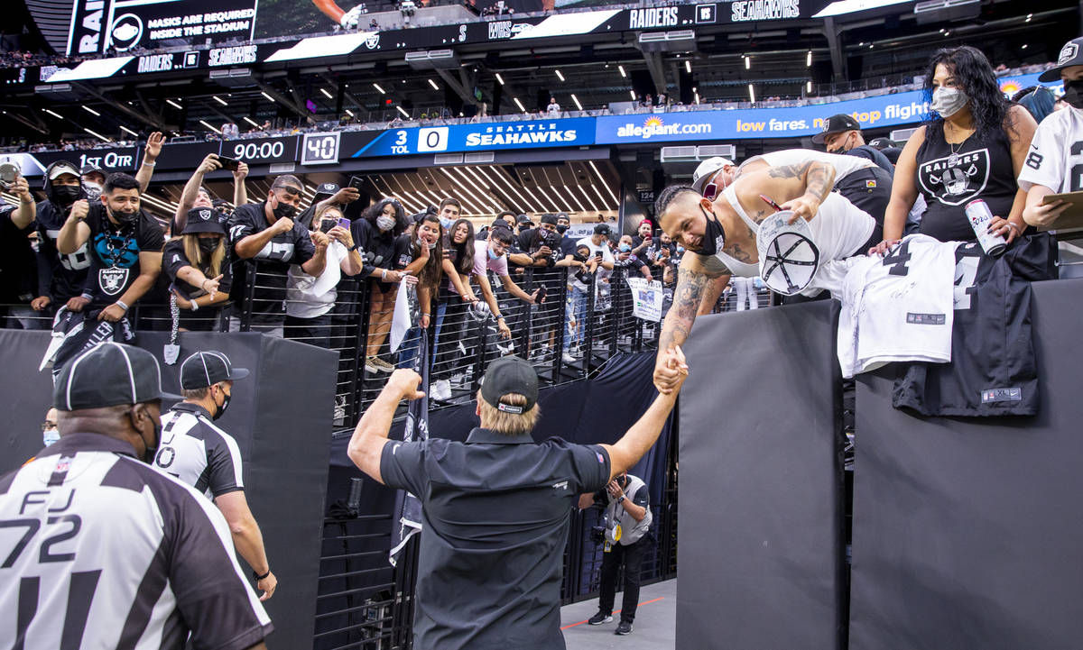 Raiders head coach Jon Gruden greets fans while leaving the field before the Raiders home openi ...