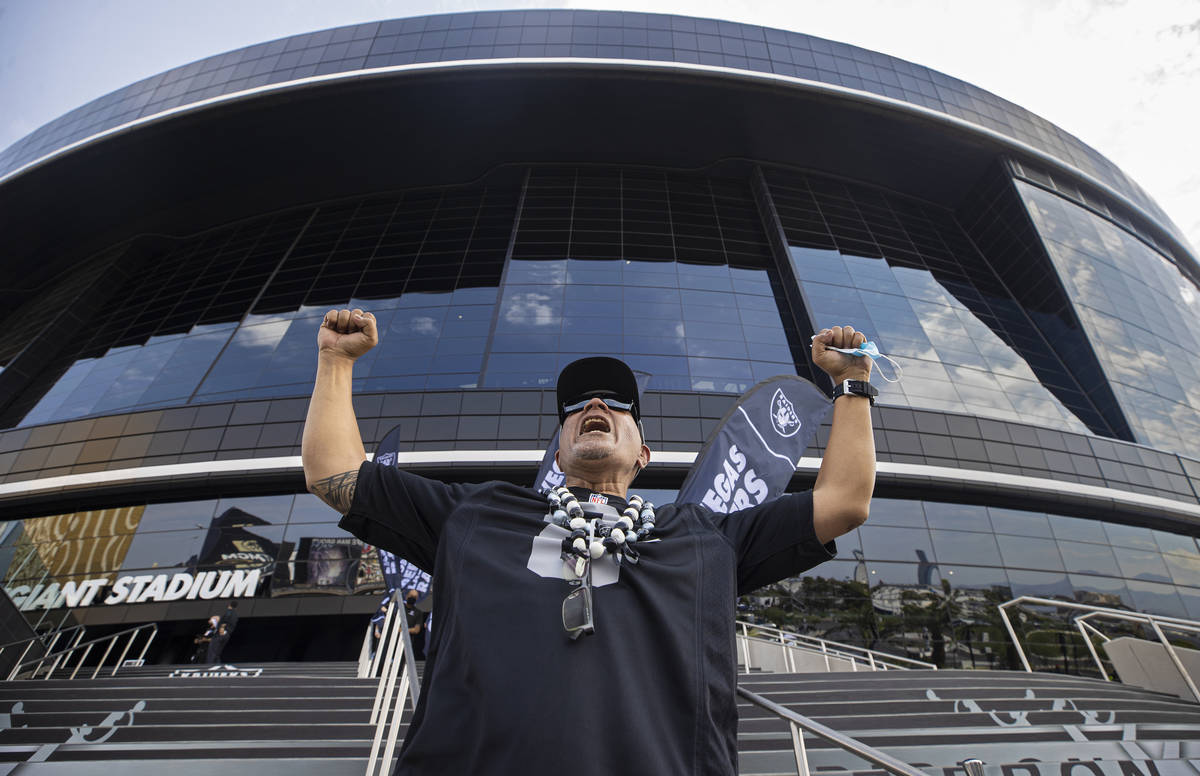 Raiders fan John Ioane celebrates outside Allegiant Stadium before the start of an NFL preseaso ...