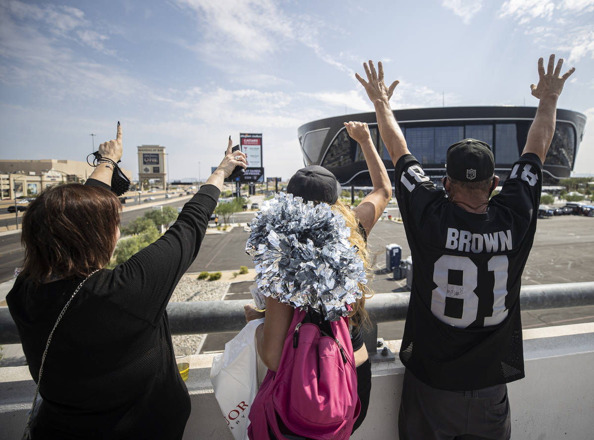 Raiders fans Laurie Rayner, left, Ginger Brown and John Gaynor cheer outside Allegiant Stadium ...