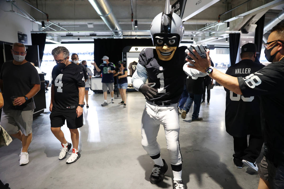 Raiders' NFL mascot Raider Rusher high fives fans while walking the concourse of Allegiant Stad ...