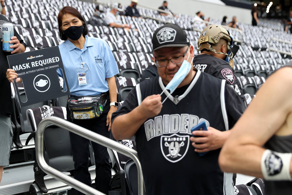 An Allegiant Stadium employee shows a mask required sign to a fan attending a NFL preseason gam ...