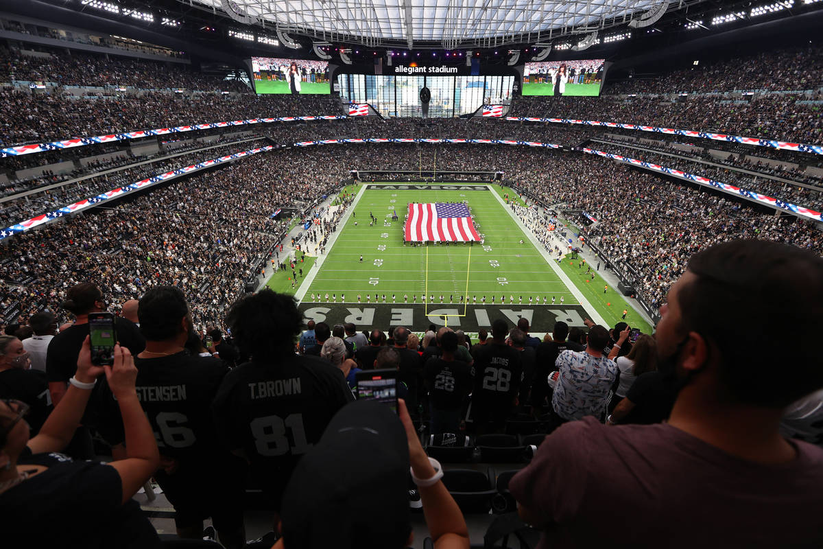 Fans listen to the singing of the national anthem before the start of a NFL preseason game betw ...