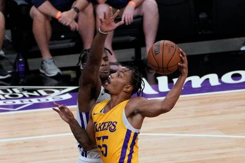 Sacramento Kings guard Davion Mitchell, left, tries to block the shot of Los Angeles Lakers gua ...