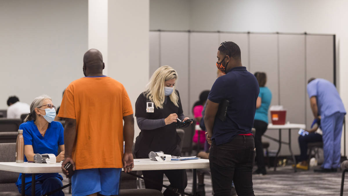 In this photo provided by Impact Church, people register for a COVID-19 vaccination at an event ...