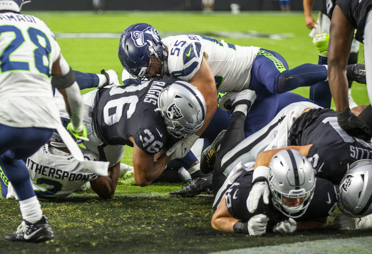 Raiders running back Trey Ragas (36) scores the first touchdown as Seattle Seahawks linebacker ...