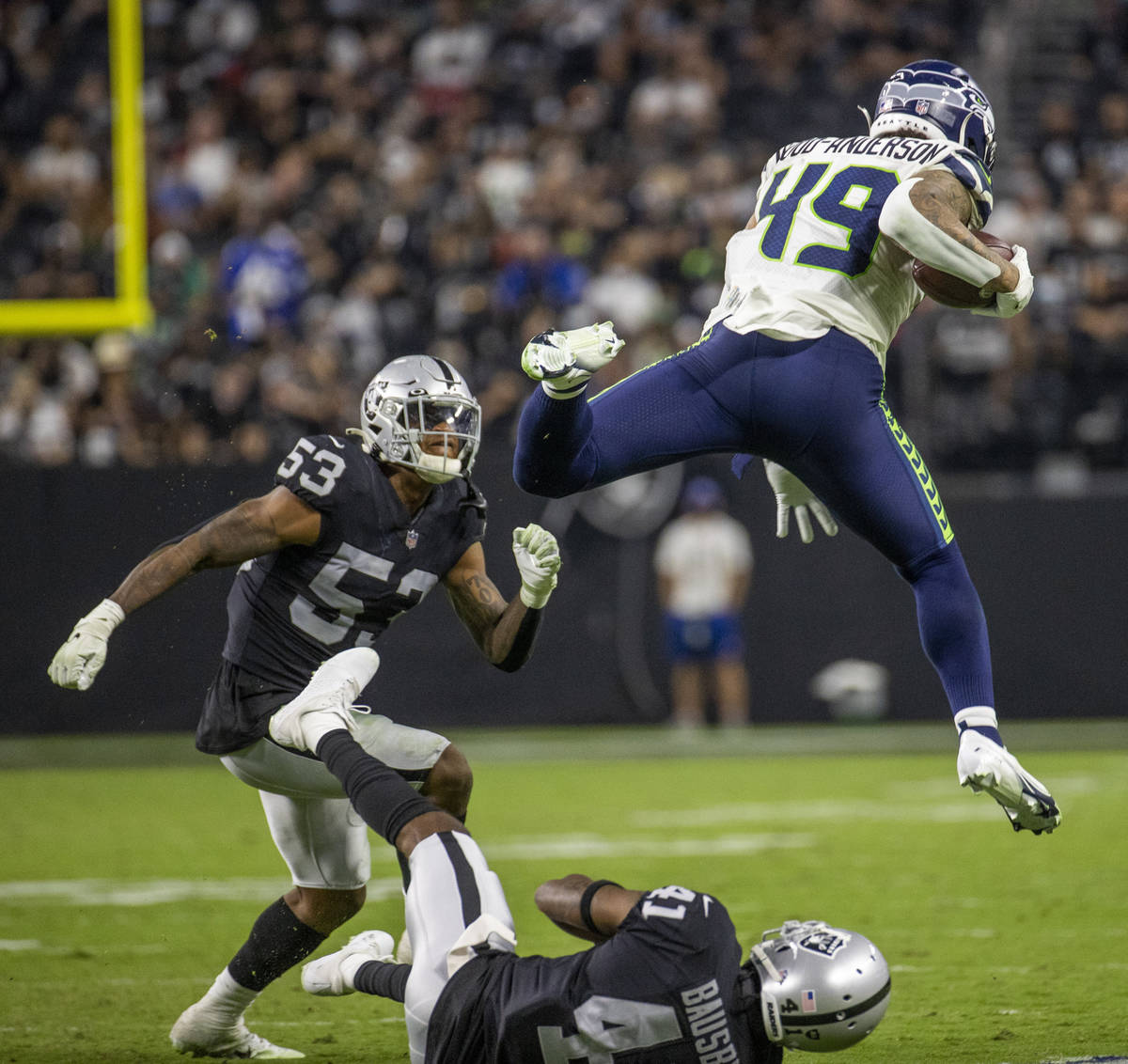 Seattle Seahawks tight end Dom Wood-Anderson (49) leaps over Raiders cornerback DeVante Bausby ...