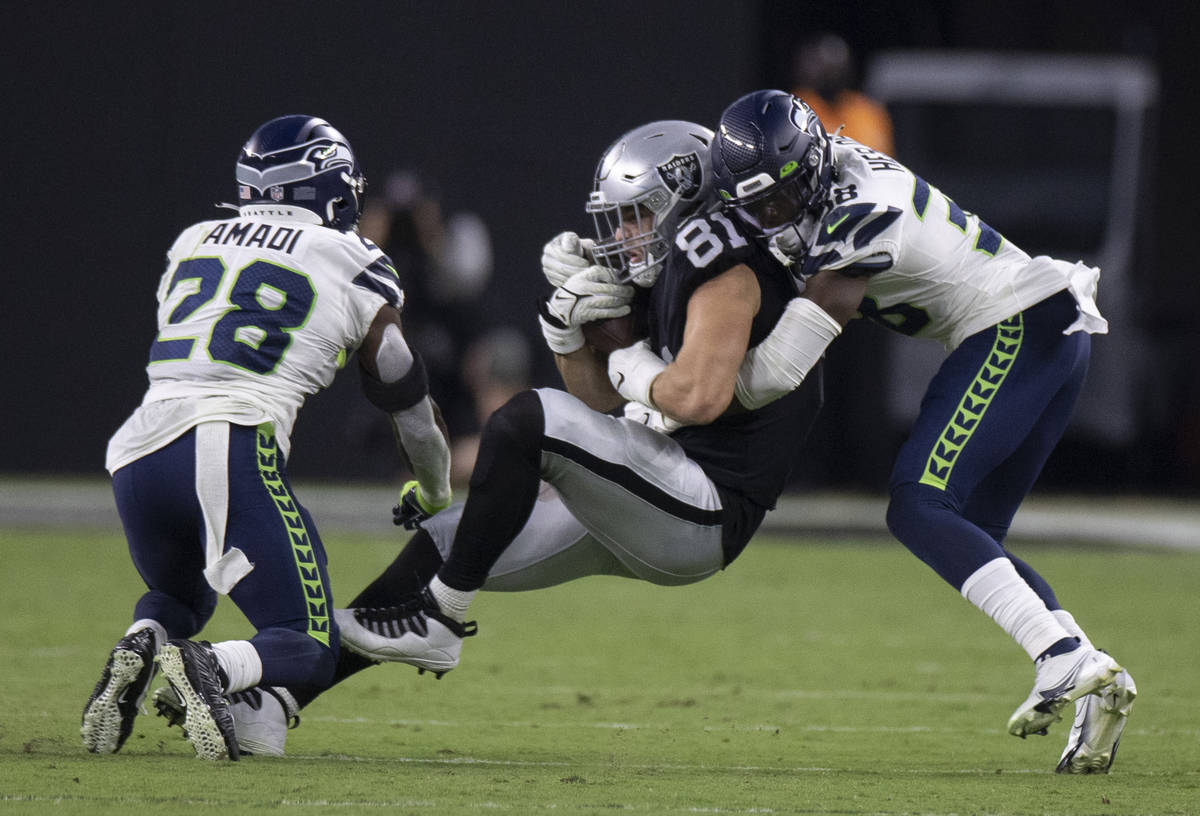 Raiders tight end Alex Ellis (81) is tackled by Seattle Seahawks defensive back Gavin Heslop (3 ...