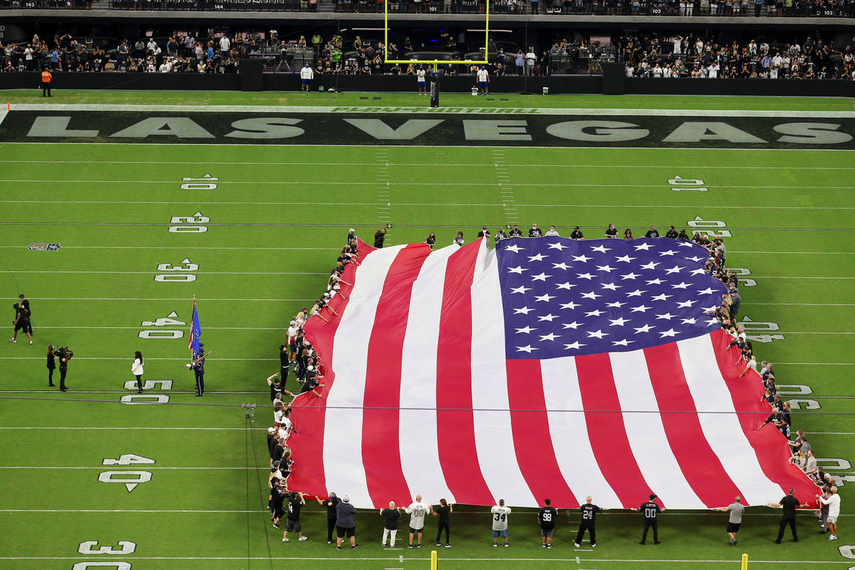 An America flag is displayed on the field during the singing of the national anthem by Marie Os ...