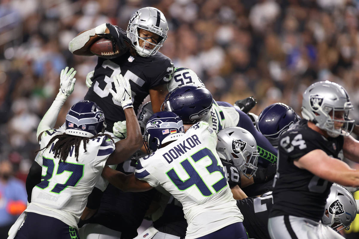Las Vegas Raiders running back B.J. Emmons (35) leaps over Seattle Seahawks safety Joshua Moon ...