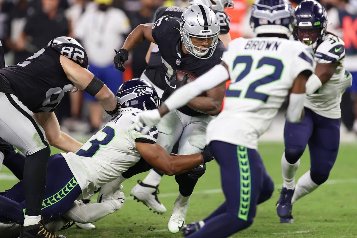 Las Vegas Raiders running back B.J. Emmons (35) is tackled by Seattle Seahawks linebacker Aaron ...