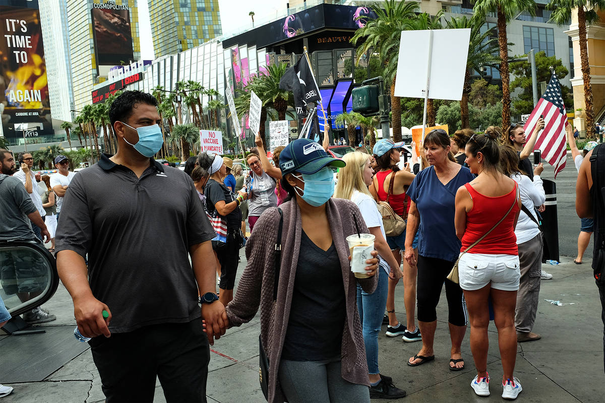 Visitors to the Las Vegas Strip, wearing masks to prevent the spread of COVID-19, pass a group ...
