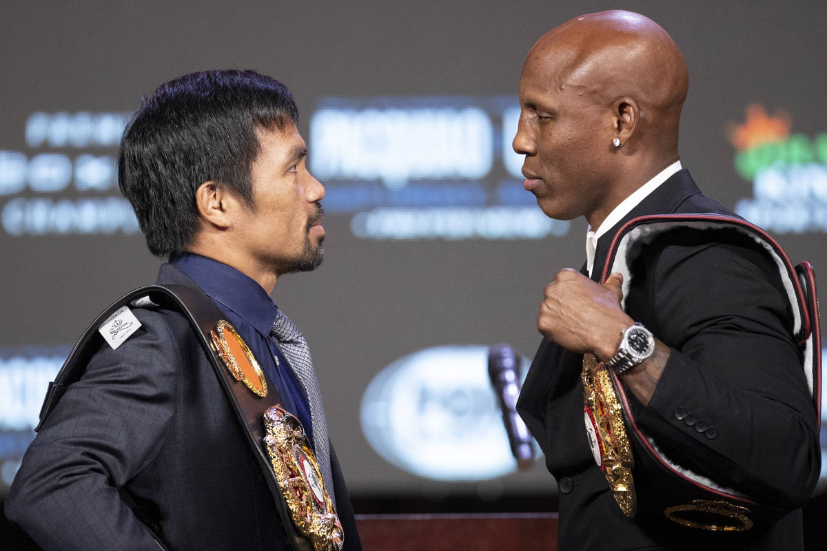 Manny Pacquiao, left, and Yordenis Ugas, face off during a press conference at the MGM Grand Ga ...
