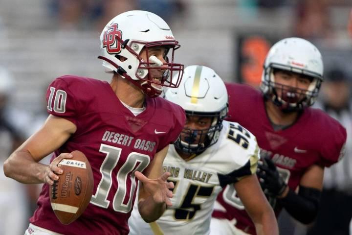 Desert Oasis quarterback Tyler Stott (10) looks to pass while Spring Valley offensive lineman T ...