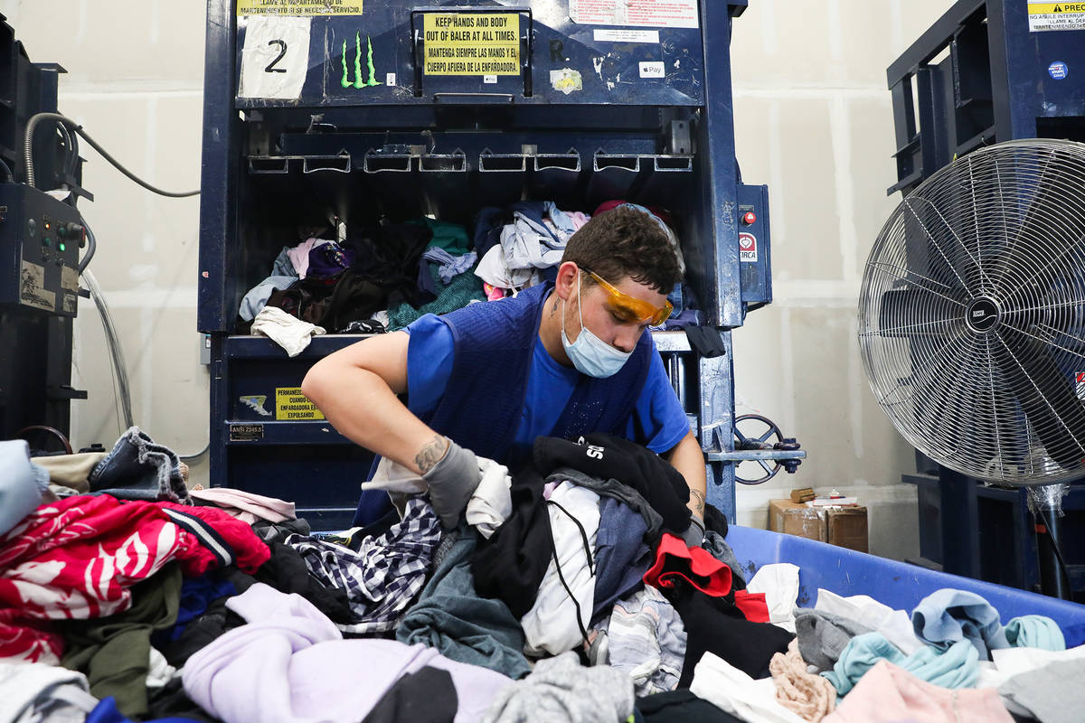 Steven Aragon picks up clothes to put in the baler at the warehouse at Goodwill Clearance Cente ...