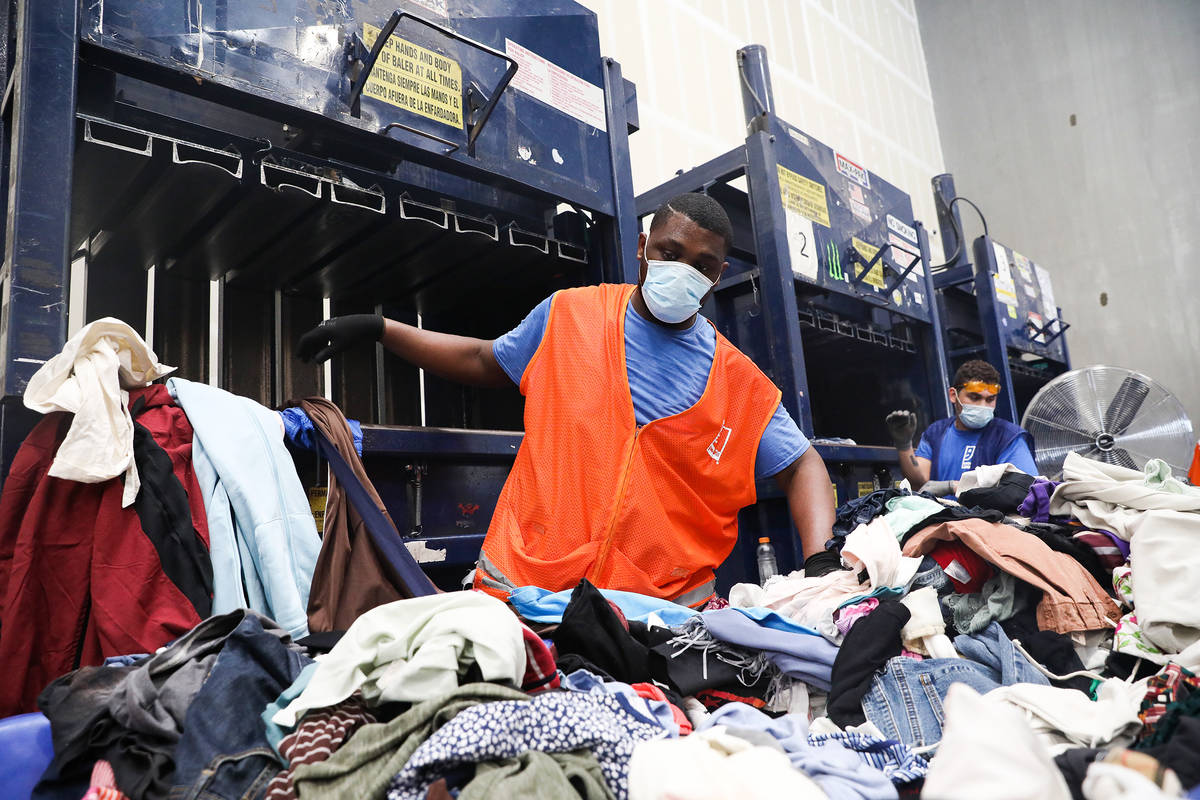 Steverson Green picks up clothes to put in the baler at the warehouse at Goodwill Clearance Cen ...