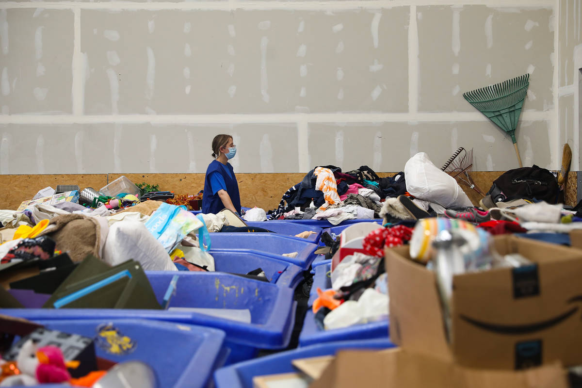 A worker moves clothes to the store from the warehouse at the Goodwill Clearance Center in Las ...