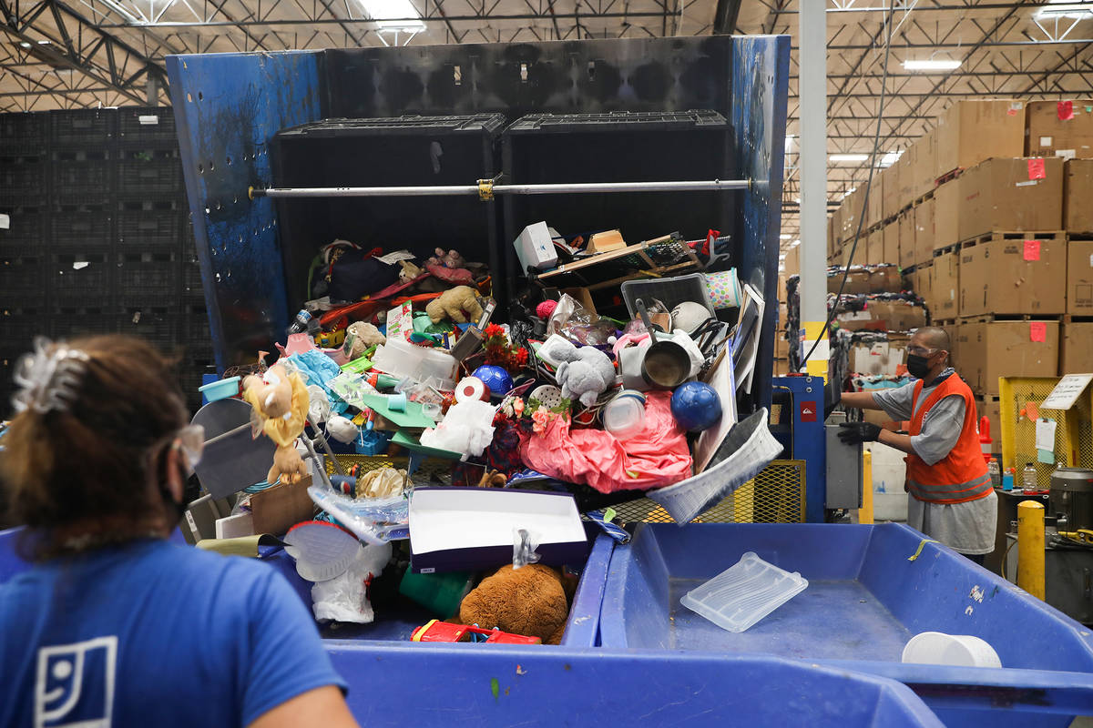 Jimmy Carrion tips donated product into a bin in the warehouse at the Goodwill Clearance Center ...