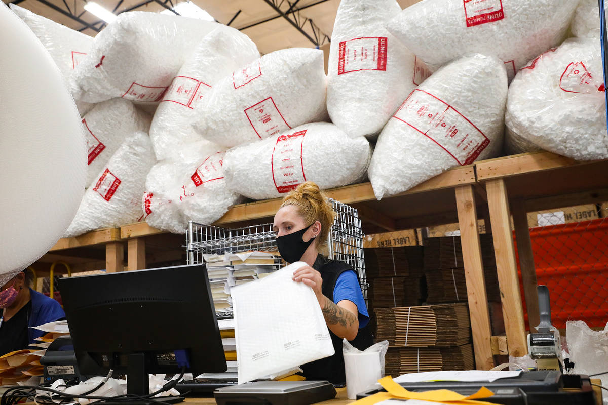Ashley Jeffries, e-commerce lead, packs items to ship in the e-commerce area at the warehouse a ...