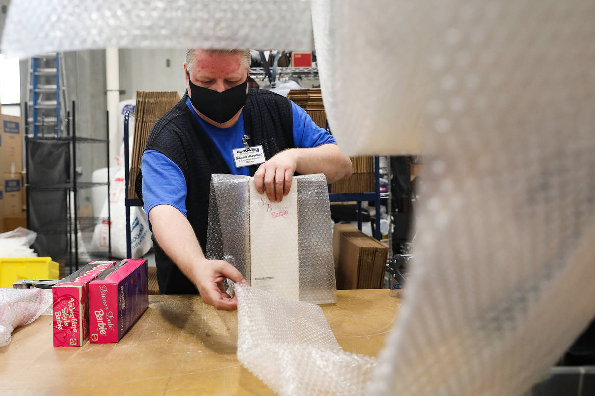 Michael Haberland, e-commerce assistant manager, packs items to ship in the e-commerce area at ...
