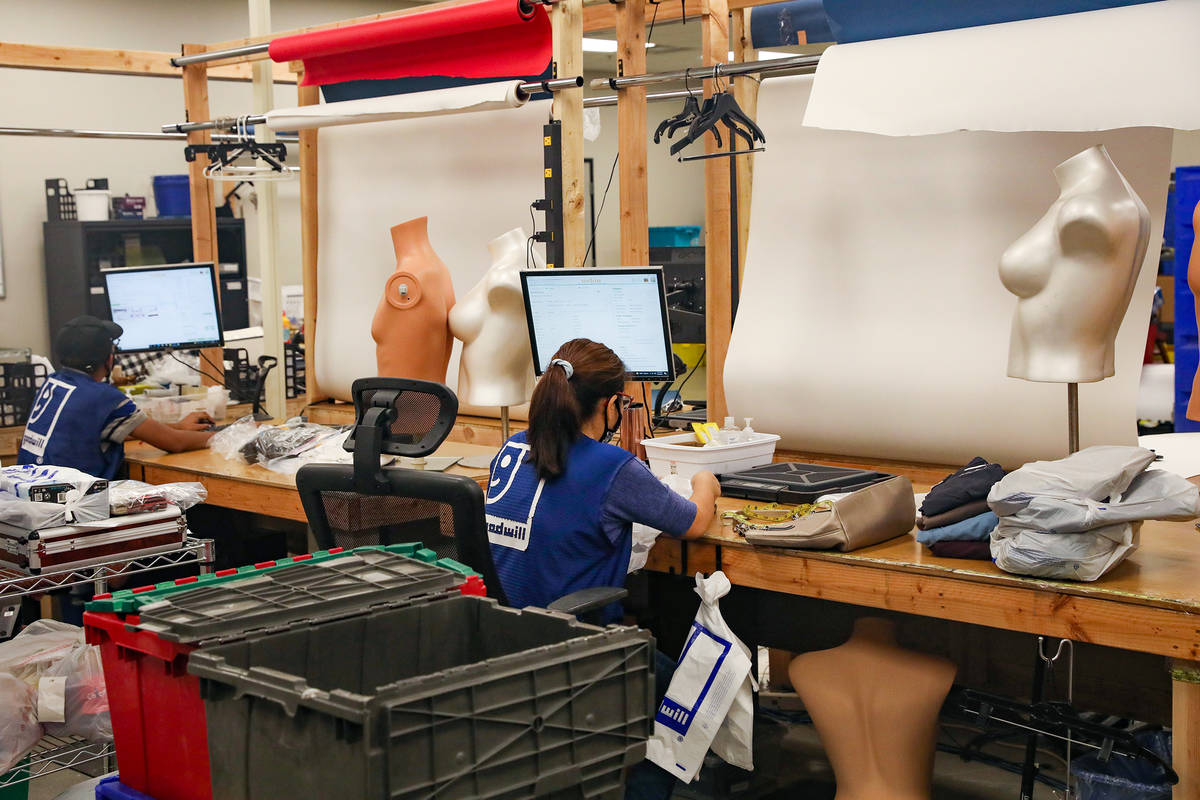 Workers list items online in the e-commerce area at the warehouse at the Goodwill Clearance Cen ...