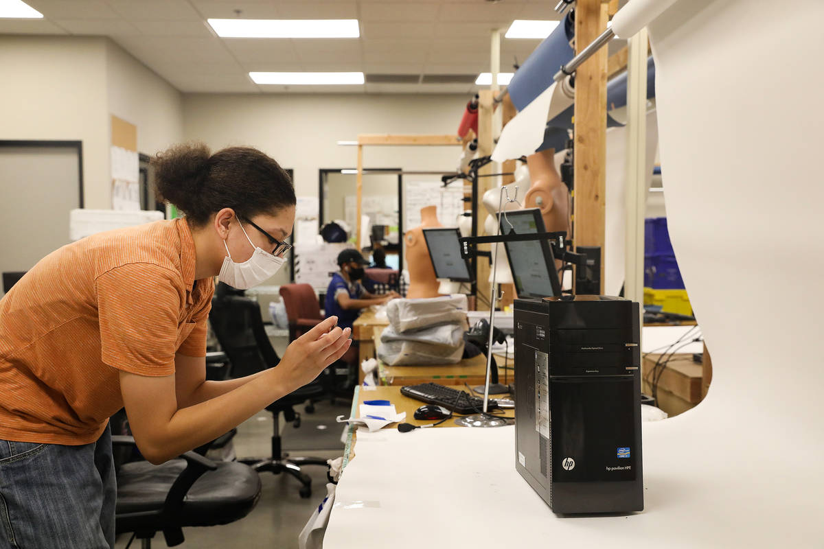 Elise Noblin, refurbishing assistant, takes photos of a donated computer modem to resell online ...