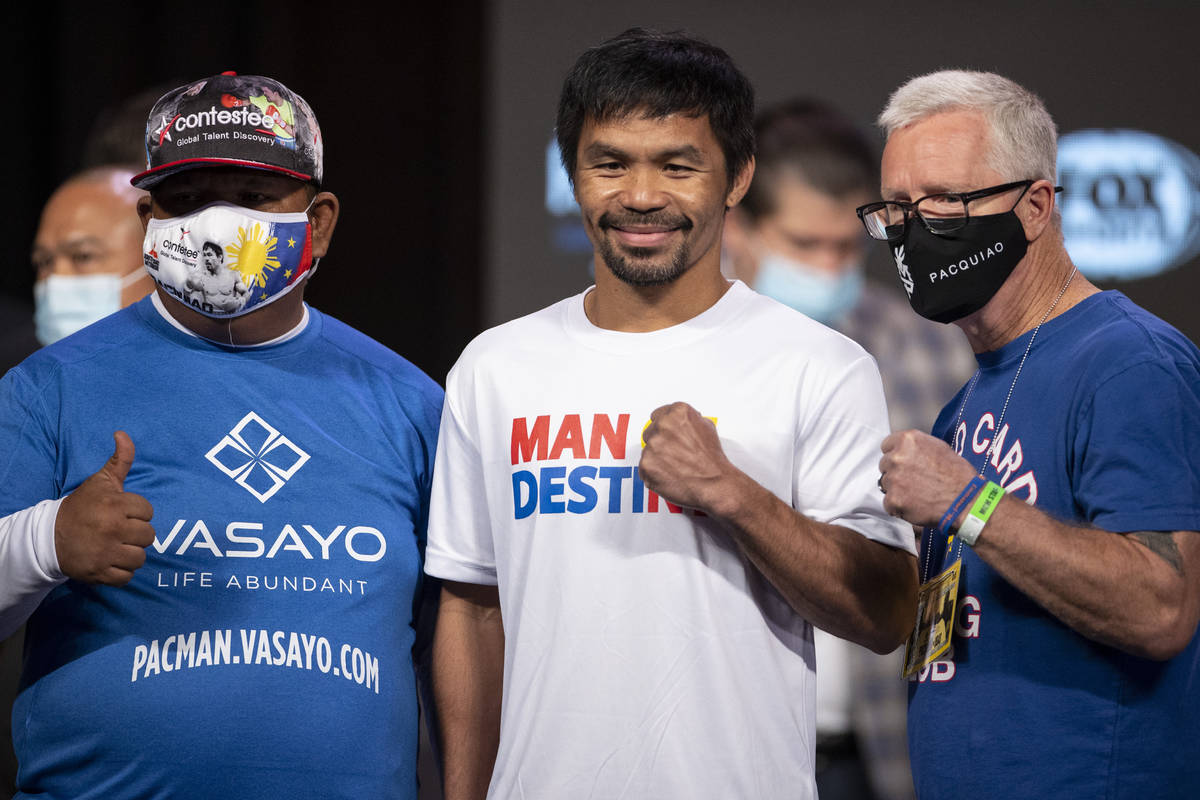 Manny Pacquiao, center, and his trainers Buboy Fernandez, left, and Freddie Roach, pose for a p ...
