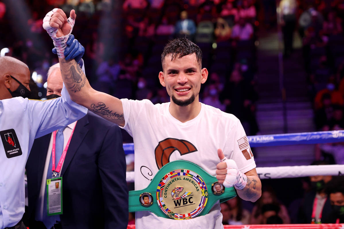 Carlos Castro raises his hands in victory after his knockout win against Oscar Escandon in the ...