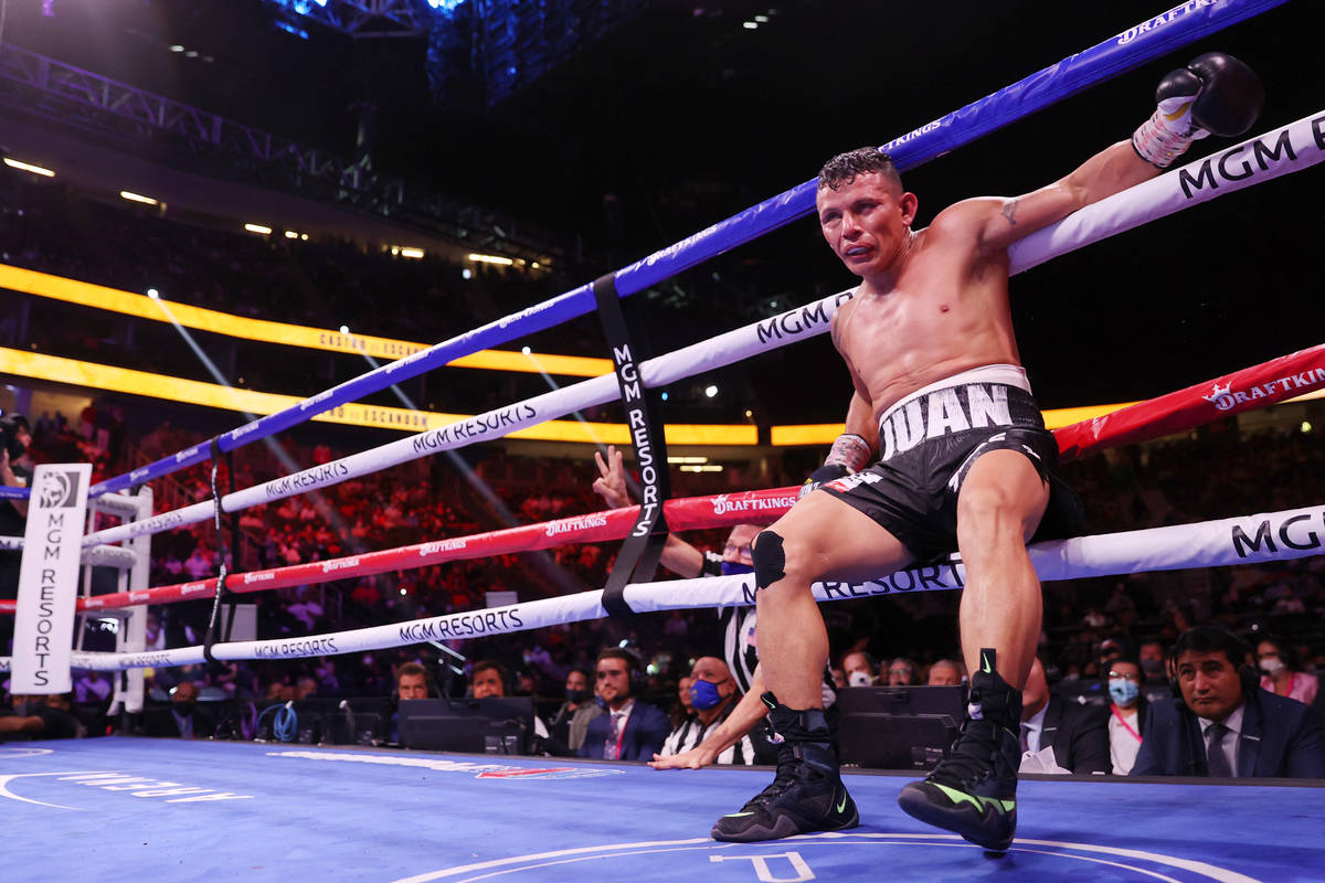 Oscar Escandon hangs to the ropes after getting knocked down by Carlos Castro in the 10th round ...