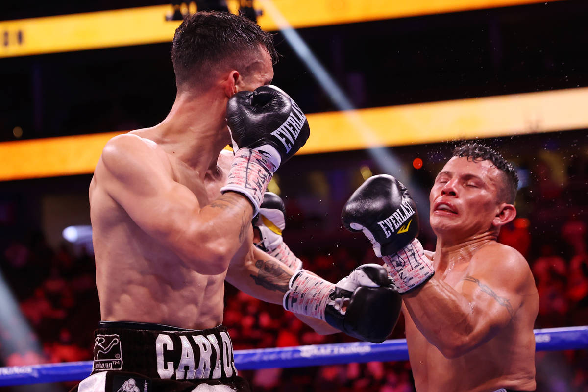 Carlos Castro, left, connects a punch against Oscar Escandon, in the ninth round of the feather ...