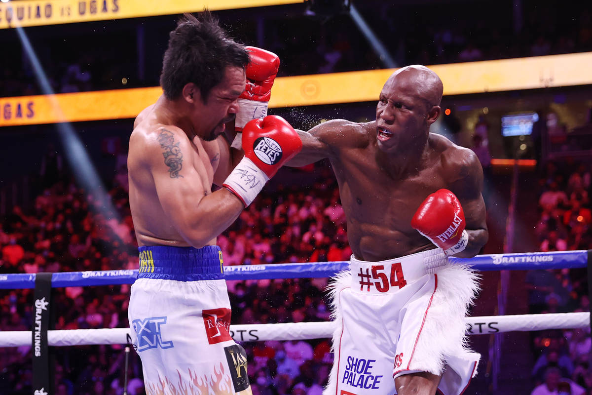 Yordenis Ugas, right, battles Manny Pacquiao in the fifth round of the WBA World Welterweight T ...