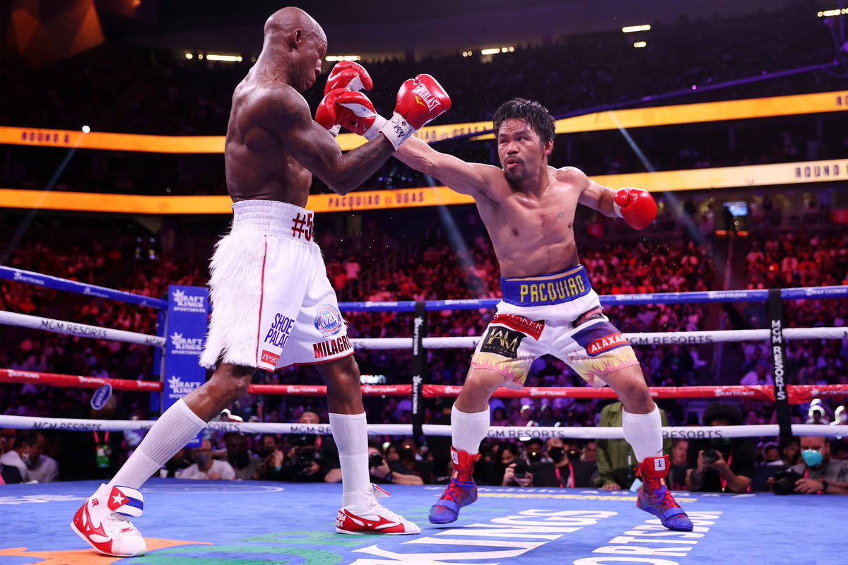 Yordenis Ugas, left, battles Manny Pacquiao in the sixth round of the WBA World Welterweight Ti ...