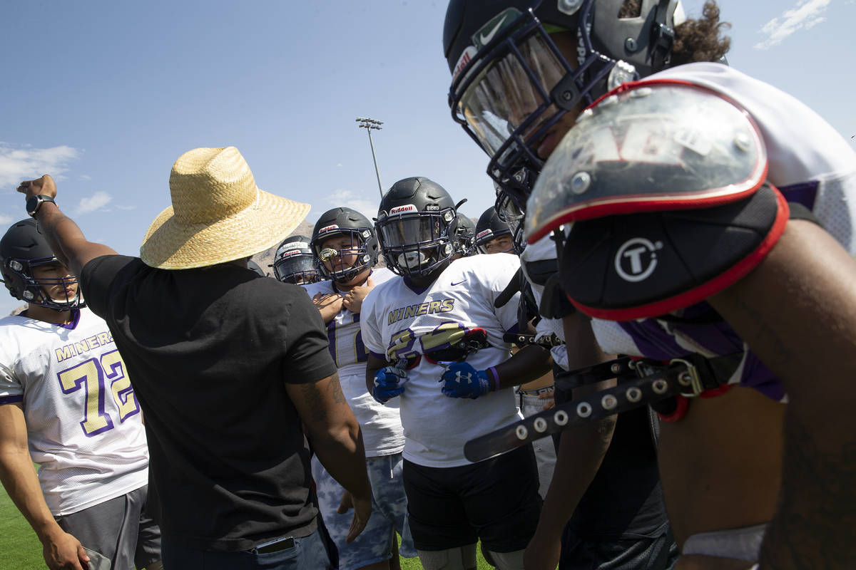 Assistant coach and defensive coordinator Tyrell Tarboro provides guidance to members of the va ...