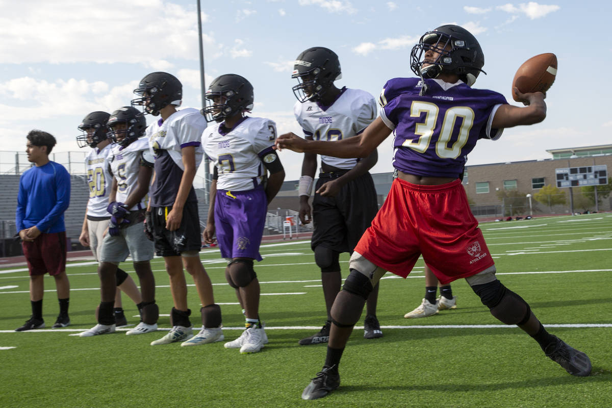 Freshman Deshawn Banks, right, participates in offensive drills during varsity football practic ...