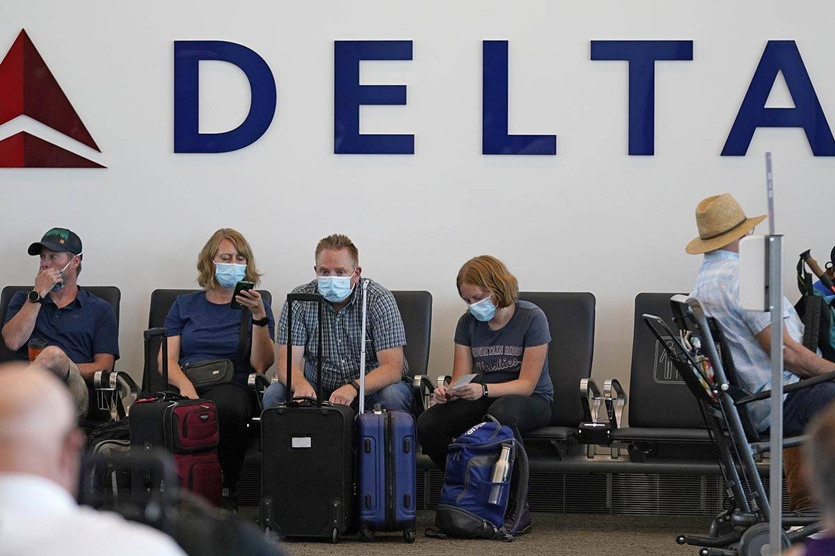 FILE - People sit under Delta sign at Salt Lake City International Airport on July 1, 2021, in ...