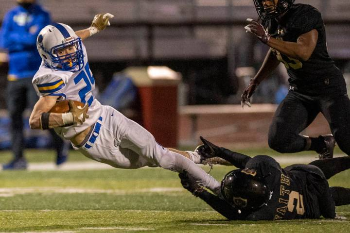 Moapa Valley's Jayme Carvajal (25) is stopped by his feet after a long pass by Faith Lutheran's ...