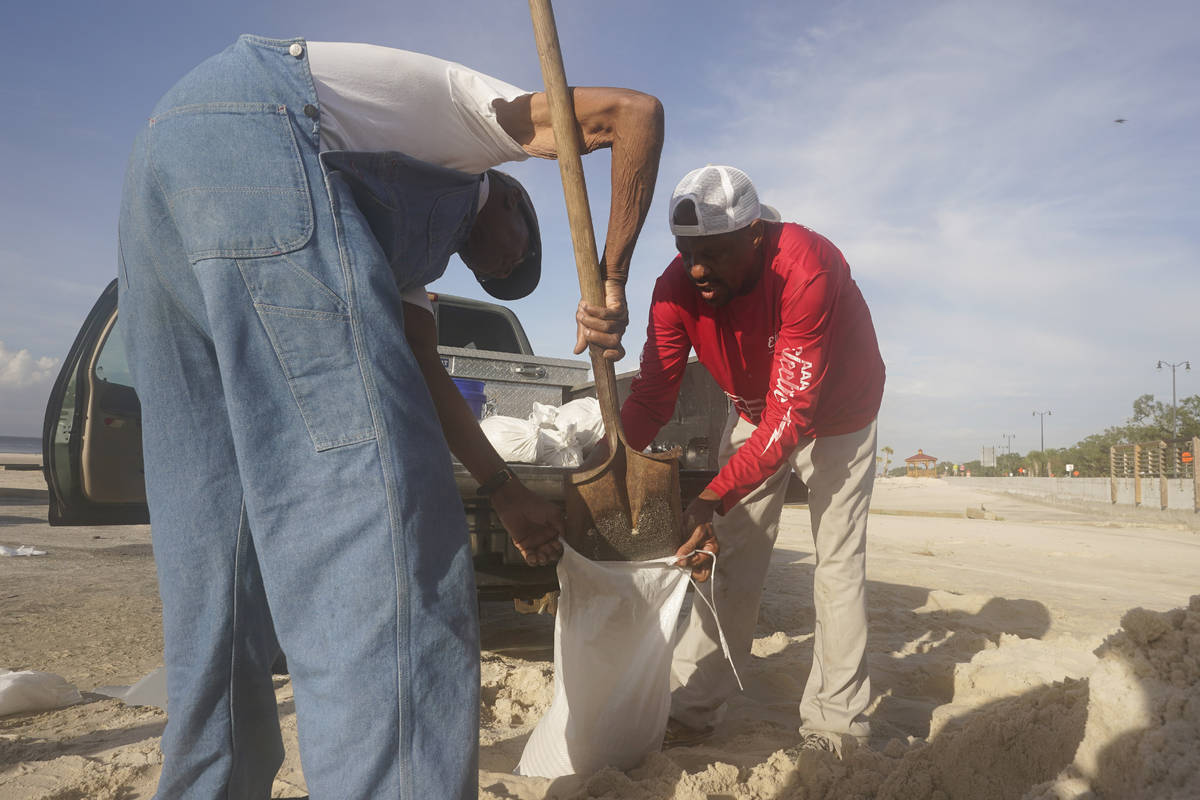 Gregory Moore, right, helps a local residents fill sand bags as they prepare for the expectd ar ...